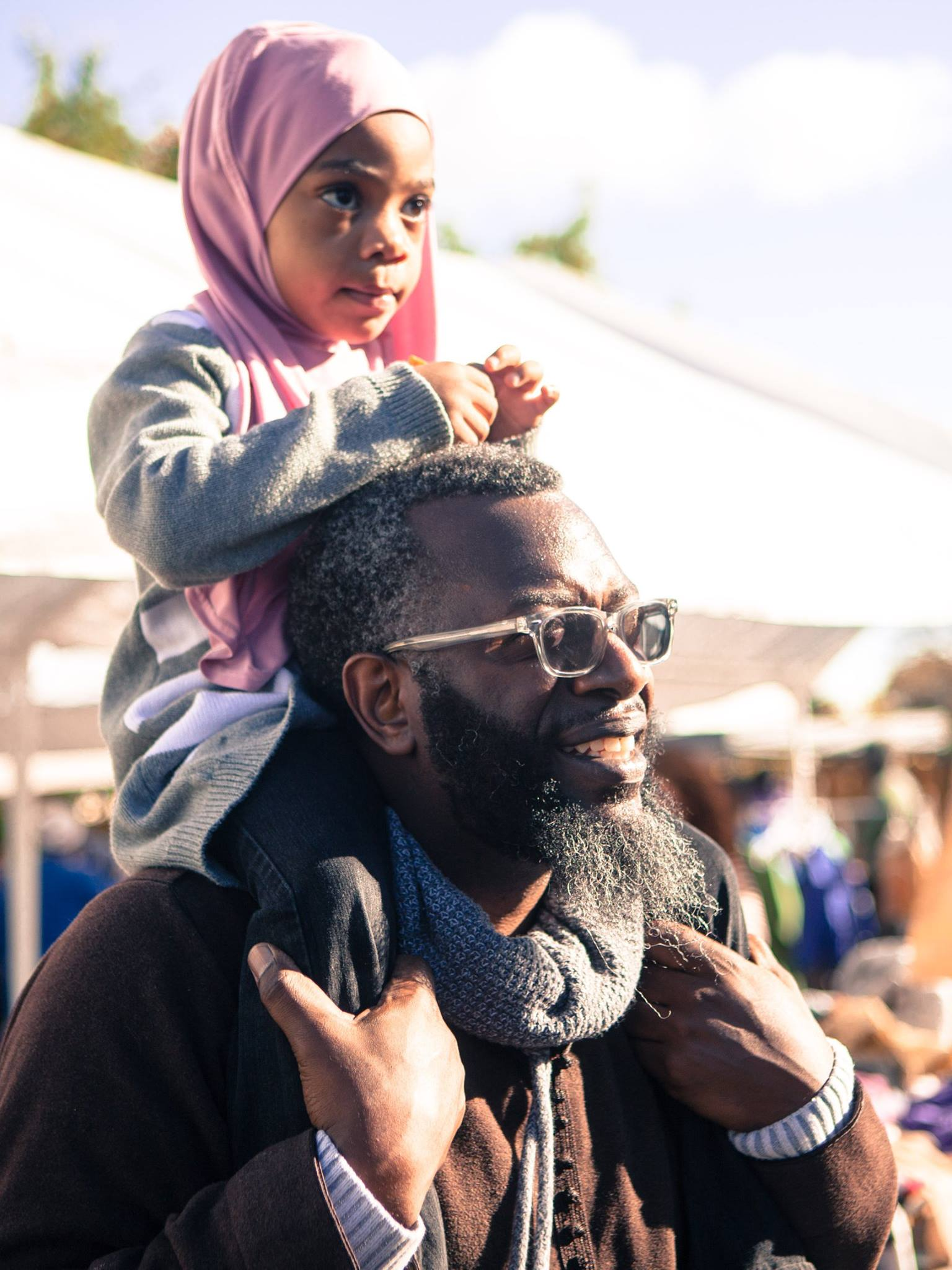 A young, African American child is sitting on the shoulders of an older, Black man. The picture is taken outside on a sunny day.