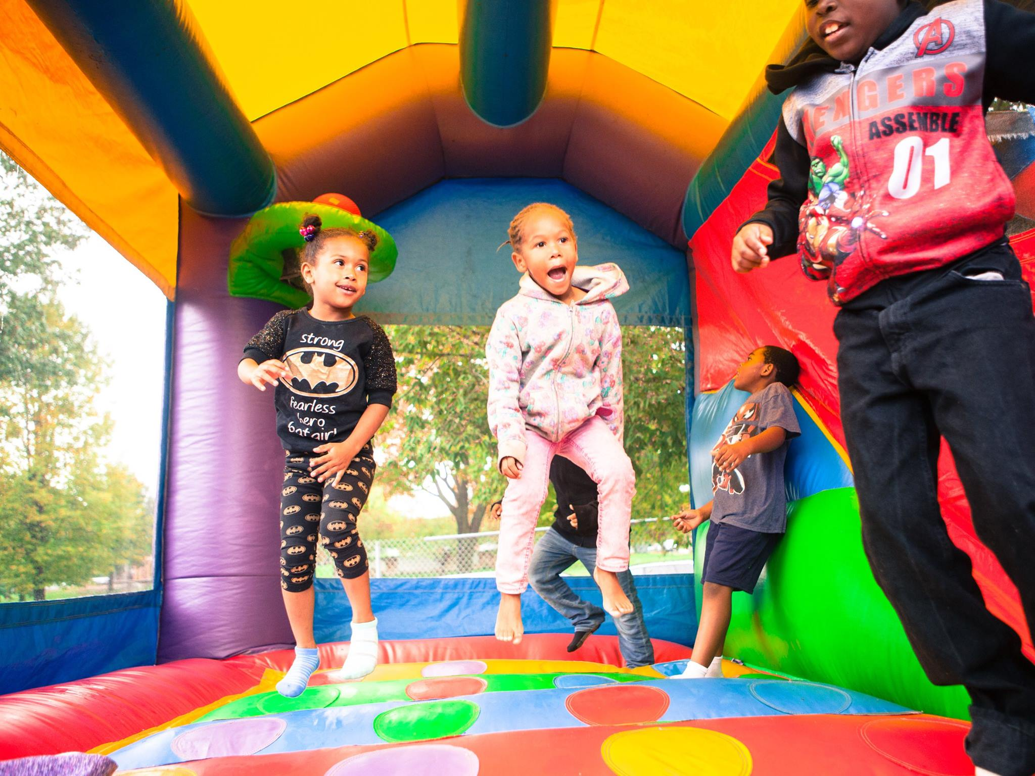A group of children joyfully jumping in a colorful bounce house.