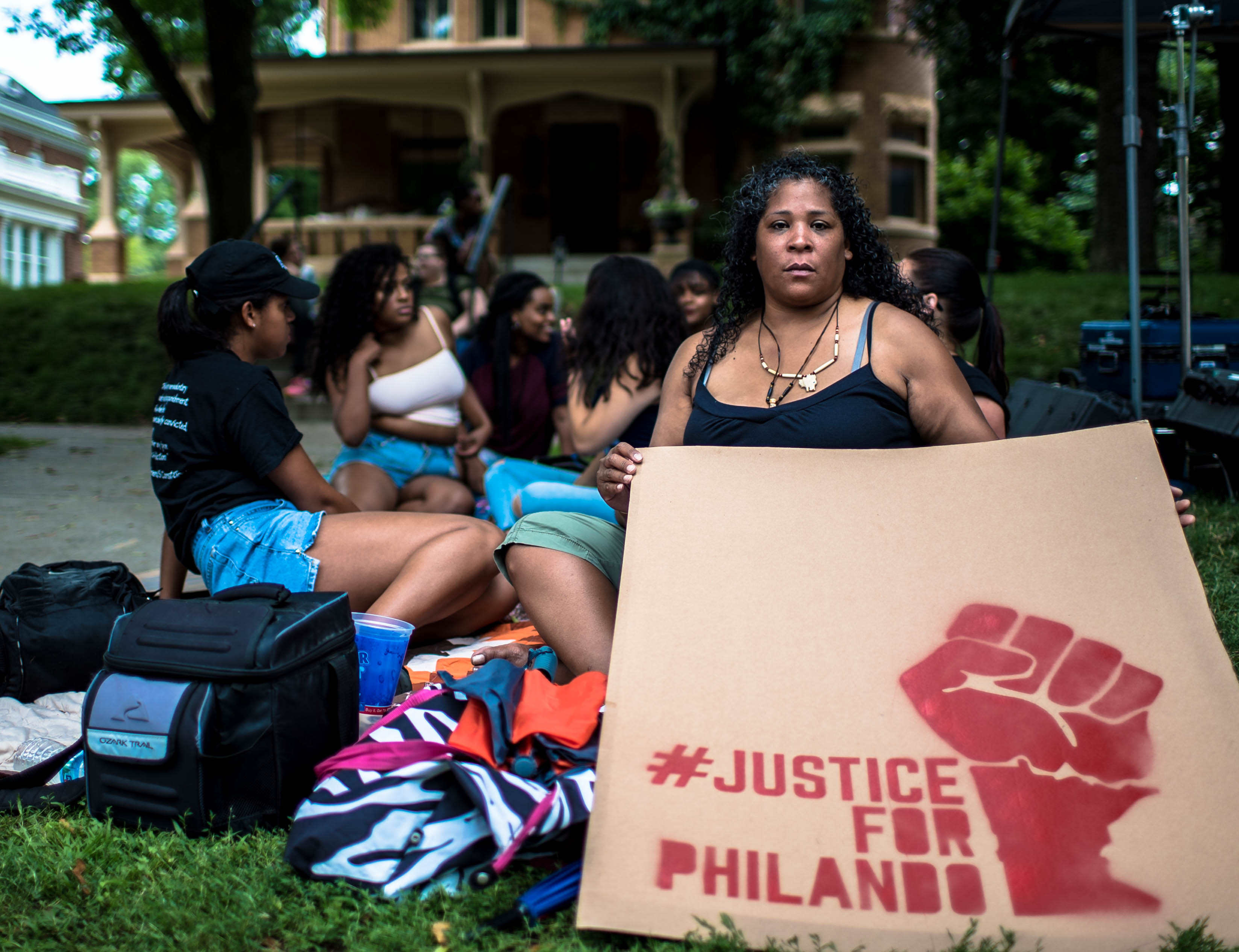 """A group of black femmes sit on a lawn in front of a house. One of them faces the camera, holding a large sign that says, """"#JustriceForPhilando."""" The sign has the black power fist with the state of Minnesota as the wrist painted on it."""