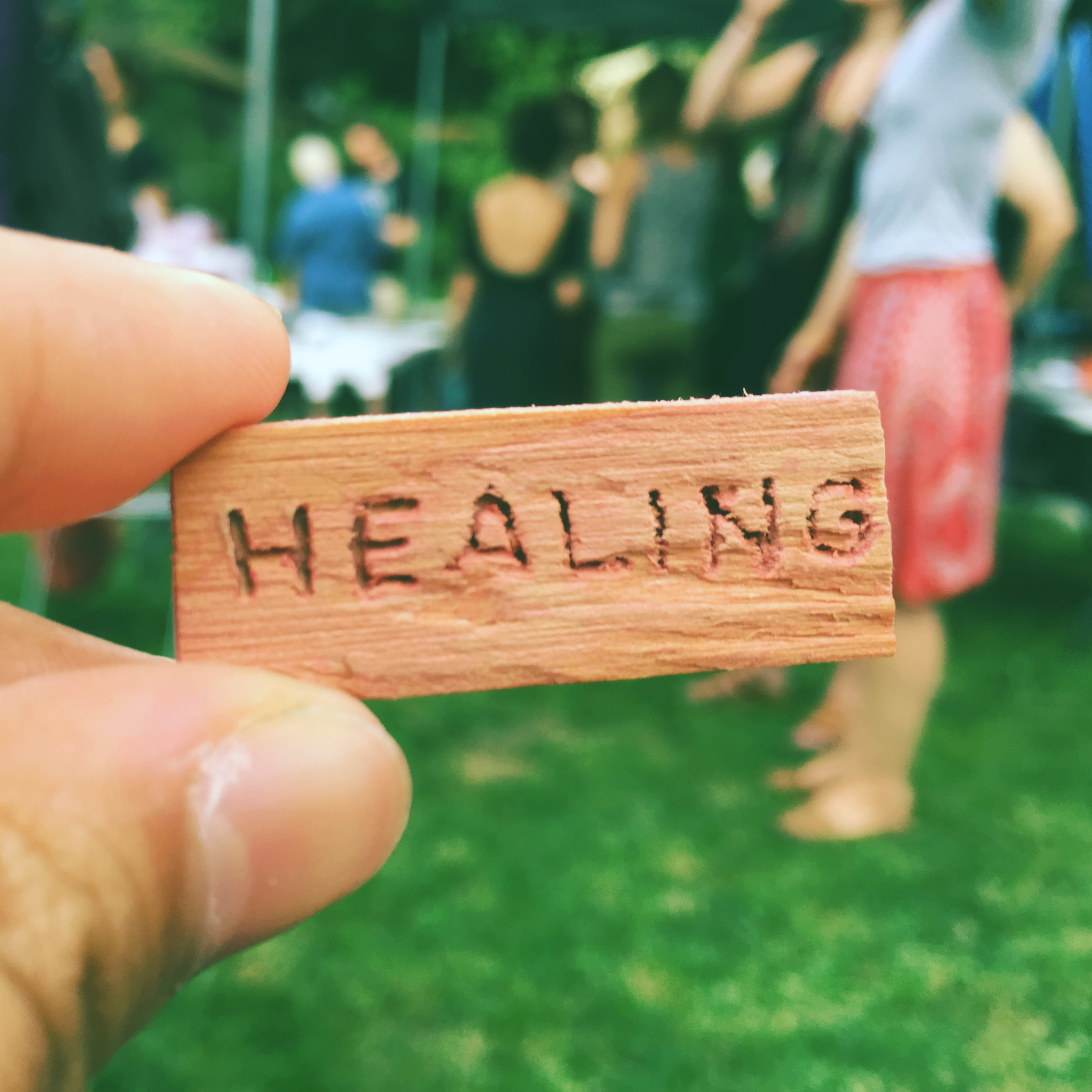 """A hand holds a small, wooden block with the word """"healing"""" carved into it. The out-of-focus background features people talking outside in a greenspace."""