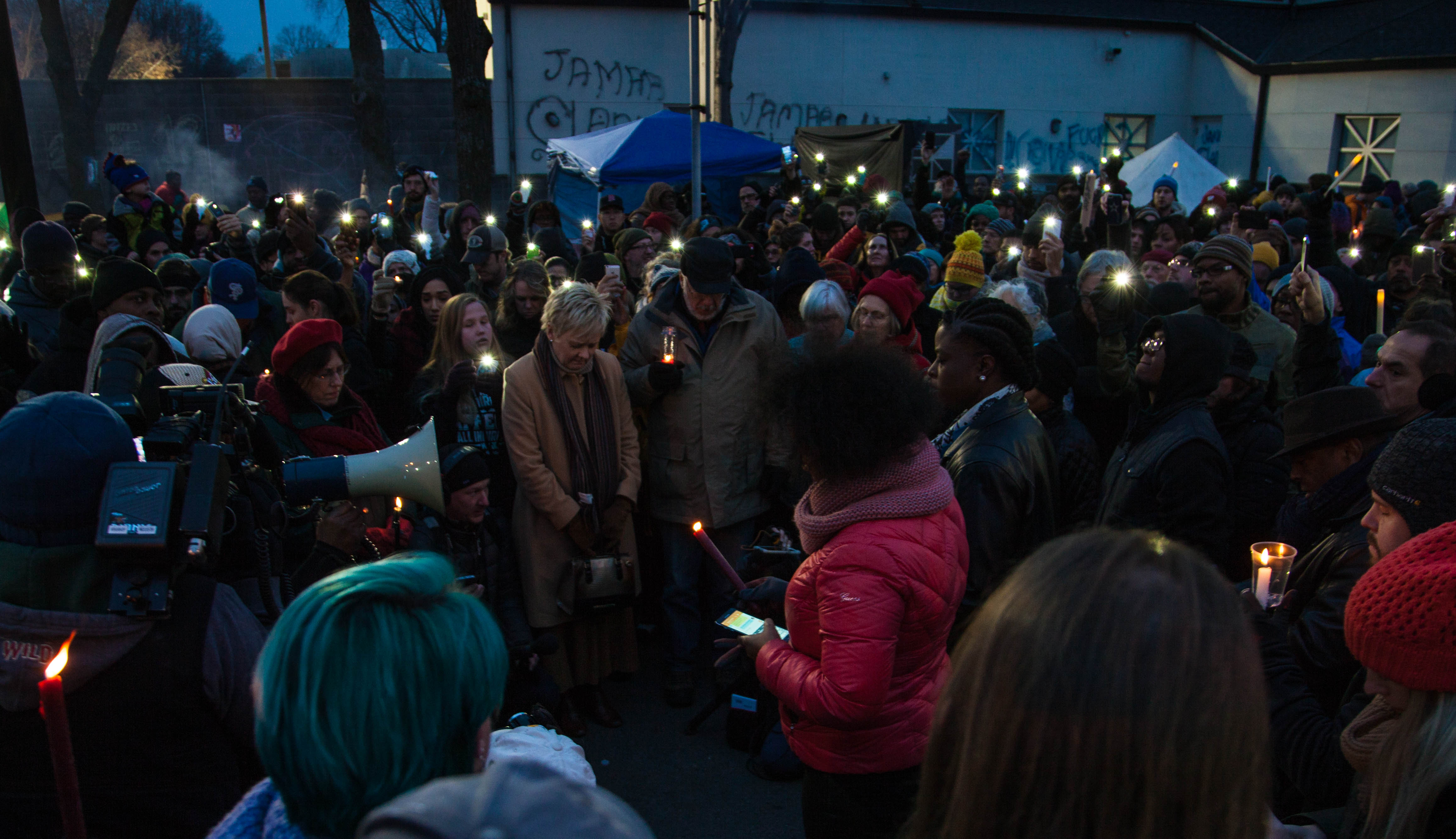 A large group of folks gathered at a candlelight vigil for Jamar Clark. It is night-time, and people have solemnly have their heads down.
