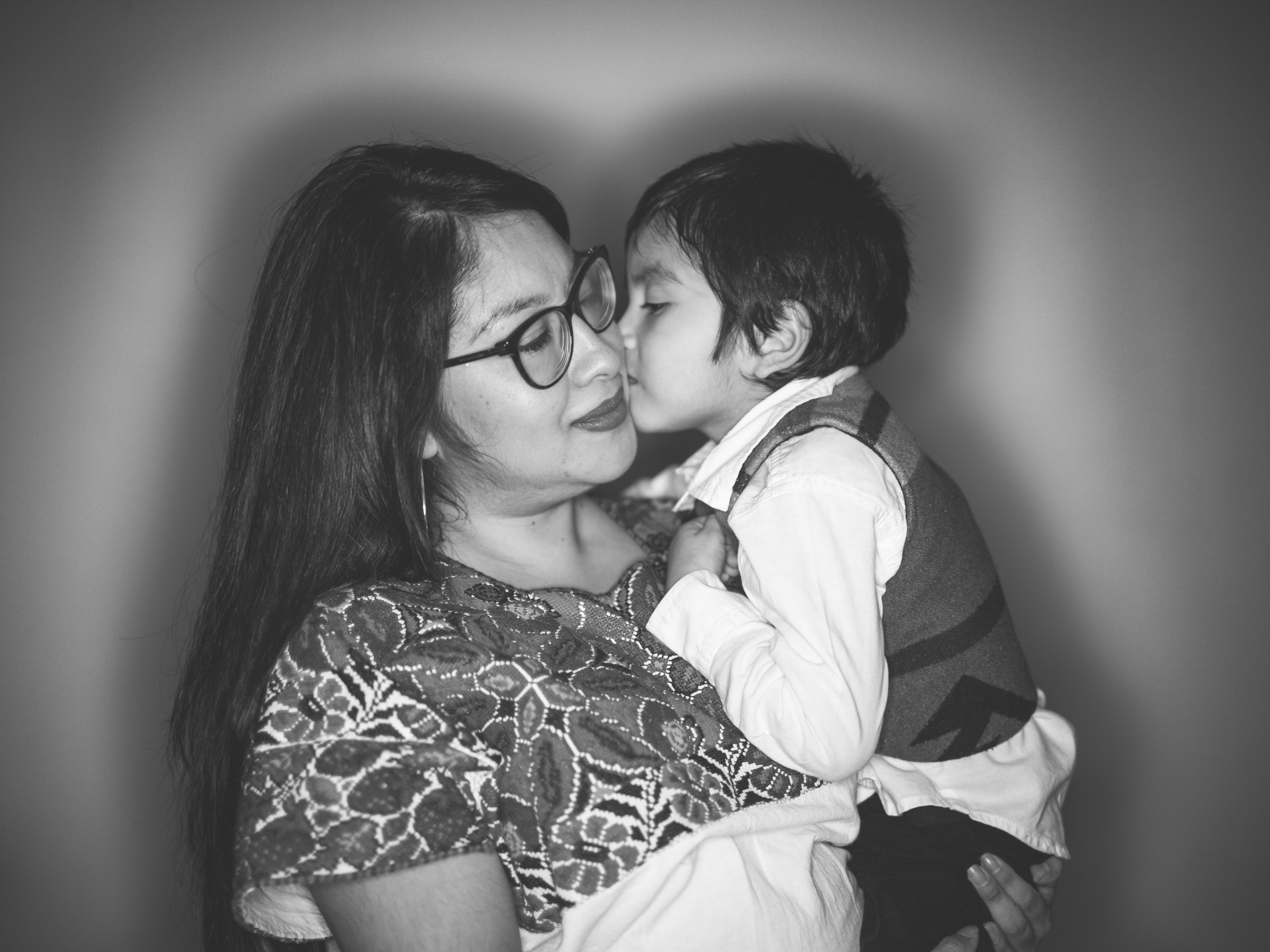 A black-and-white photograph of a woman with her eyes closed, carrying a child in her arms. The child is lovingly kissing her cheek.