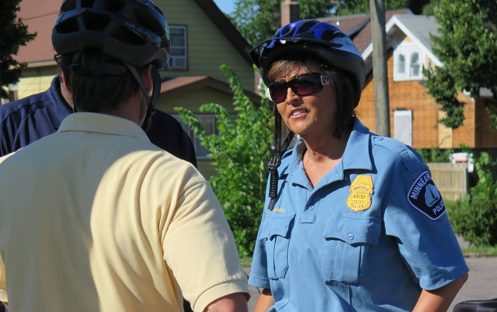 Former Minneapolis Police Chief Janee Harteau stands in a blue uniform and bike helmet.