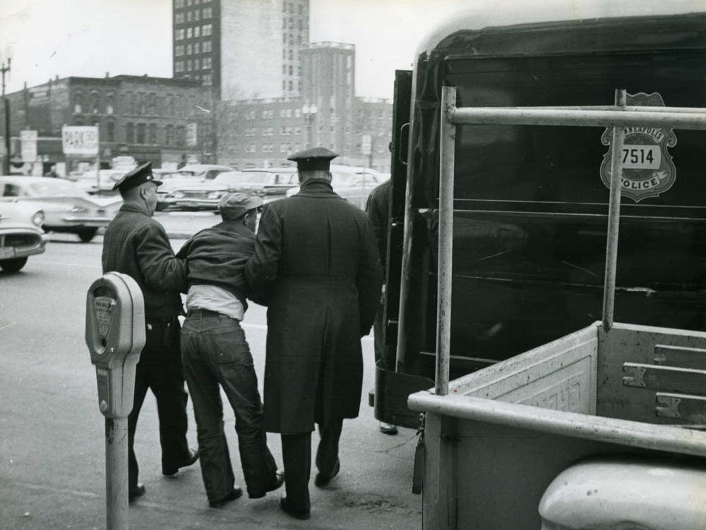 A black and white photo of two police from the back arresting a man.