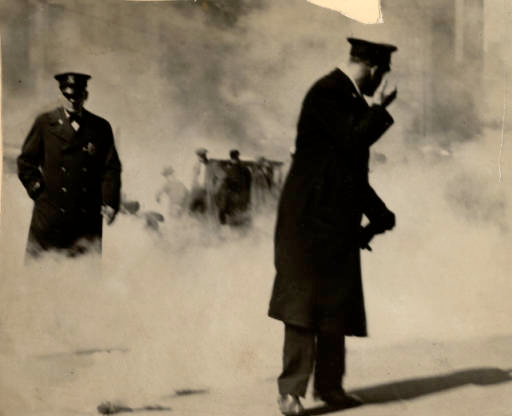 Two police stand in the foreground of the photo amidst a large cloud of smoke, strikers can be seen standing in the background.