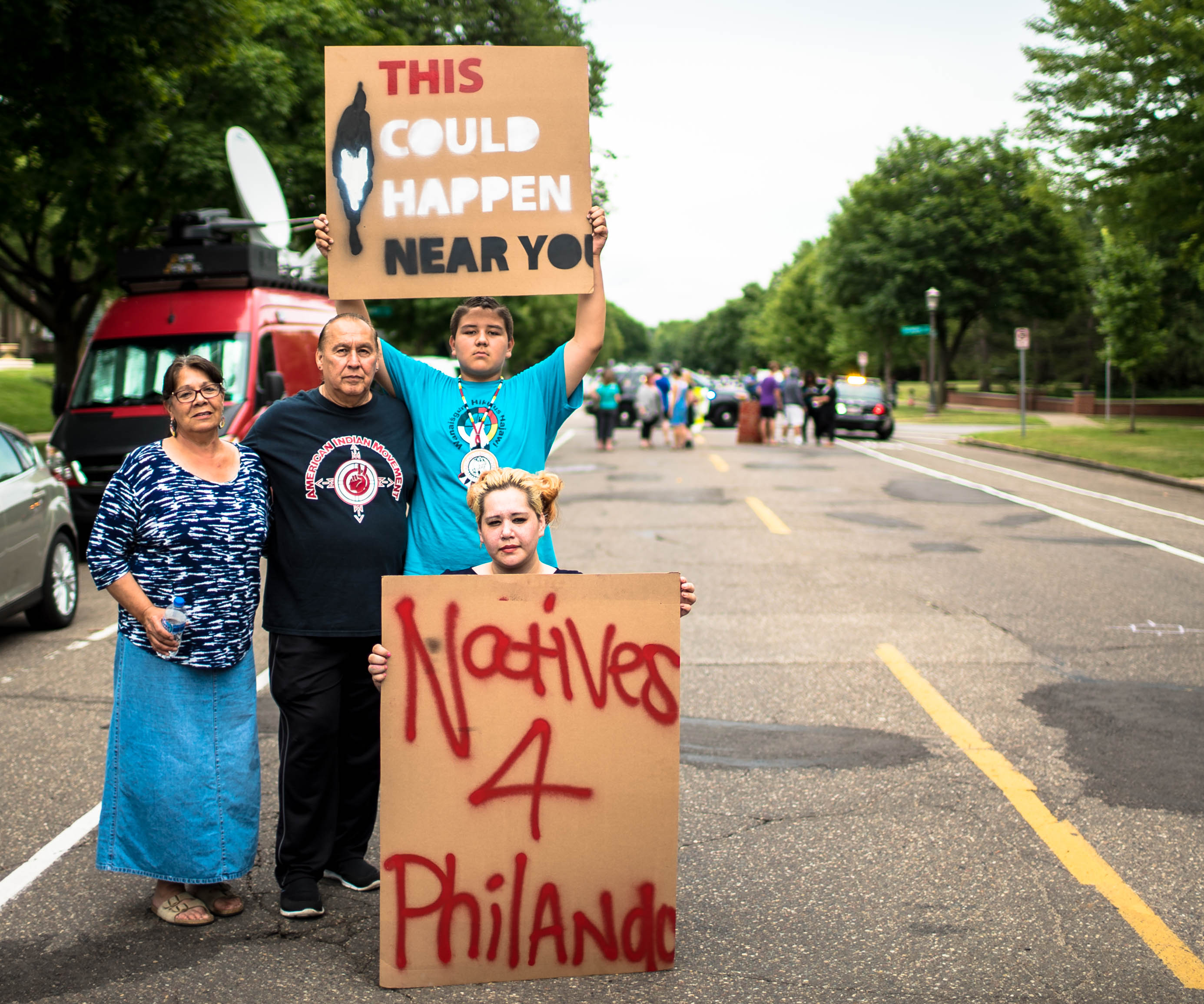 """A group of 4 Native American folks stand on the side of a blockaded road. They hold signs reading, """"Natives 4 Philando,"""" and """"This could happen near you."""""""