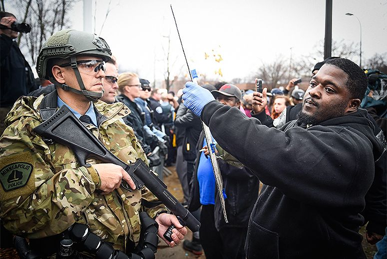 A black protester holds a sign high in the face of a white police officer, the police officer is wearing camo uniform and holding a less lethal weapon.
