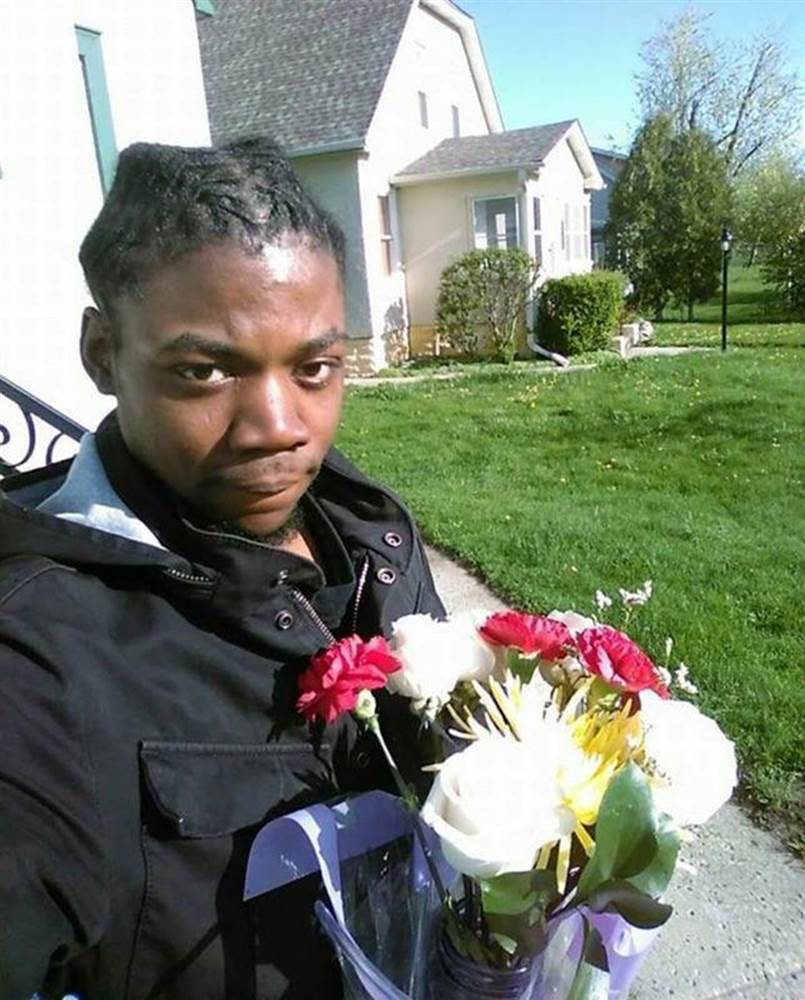 Jamar Clark stands in the sun with a bouquet of flowers.