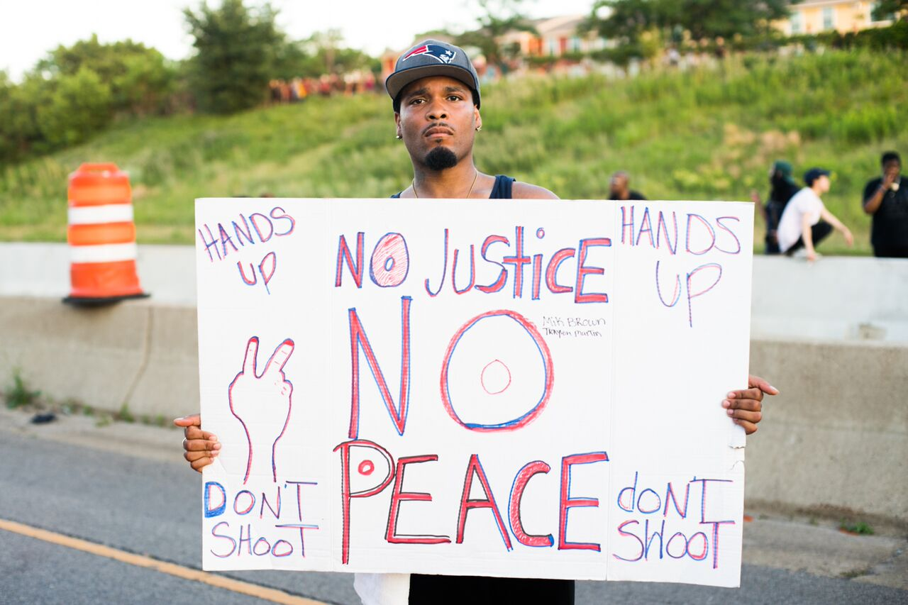 Protester stands with a sign reading, No Justice No Peace, Hands up, don't shoot.
