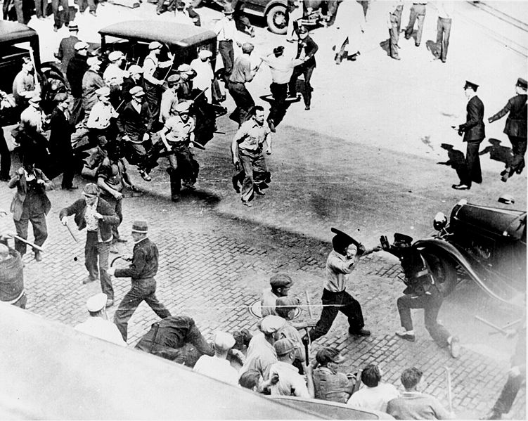 Black and White photo from 1934, teamsters and police can be seen with batons raised, ready to strike.